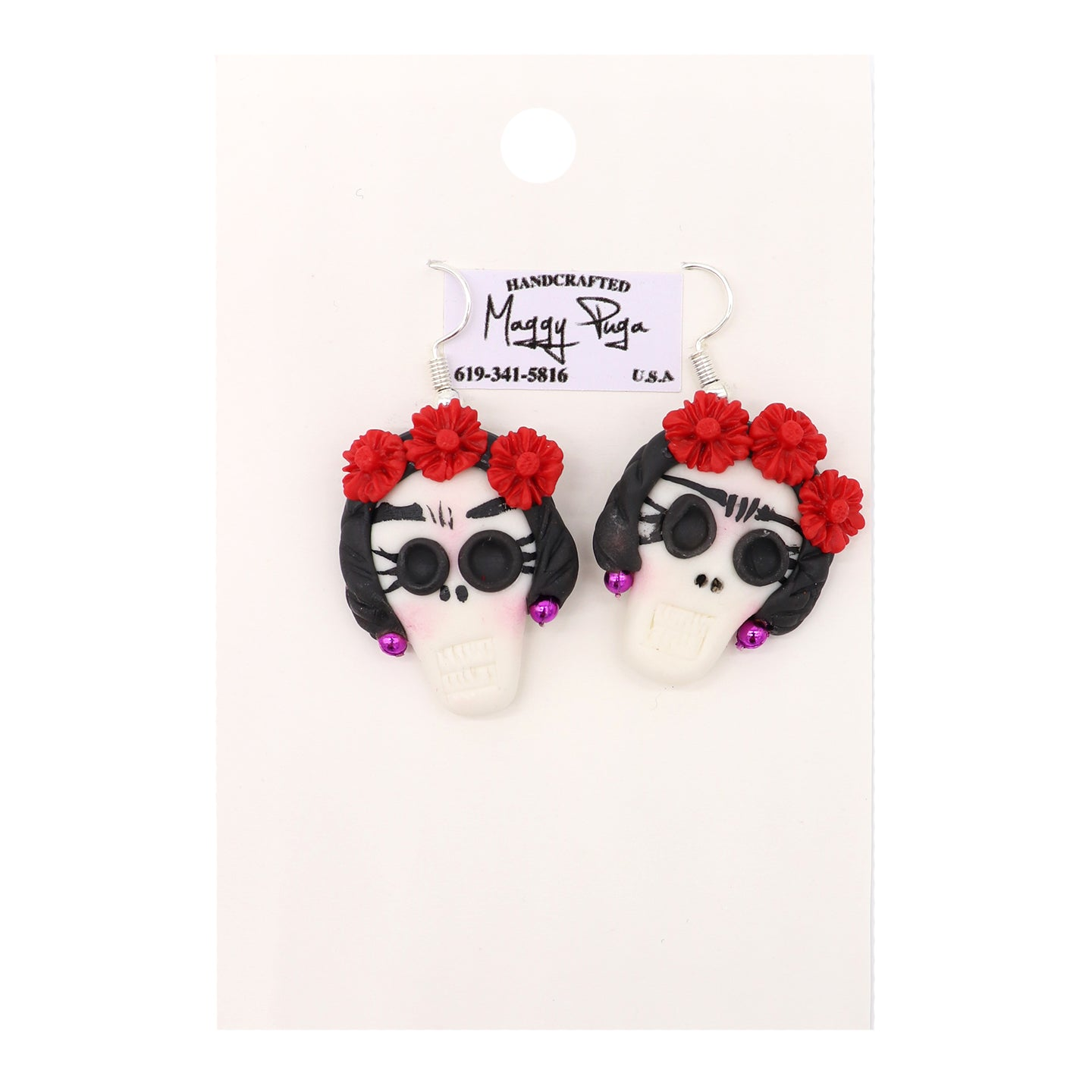Sugar Skull Earrings handmade featuring Frida Kahlo, Mexicnan Painter. Handcrafted by small shop Maggy Puga. White skulls with dark hair, unibrow, colorful red flowers, and purple earrings. Sold by SDTrading Co.