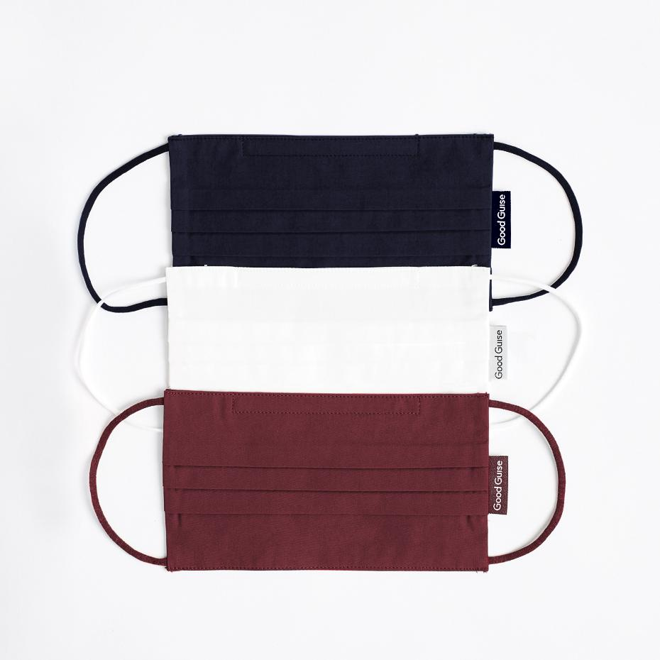 Overhead picture featuring the three colors of facemasks that come in this package, Ash, Burgundy, and Off White. with a Good Guise Tag on them