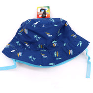 Kids bucket hat with built in UV protection, UPF 50+ for infants, toddler, and small children. Built in sun protection. Lightweight hat for sunny days, beach, pool, zoo, and playdates. Navy blue hat featuring palm trees, surfboards, and sharks in different solid colors, with baby blue Velcro straps. Reverses to solid Navy ha