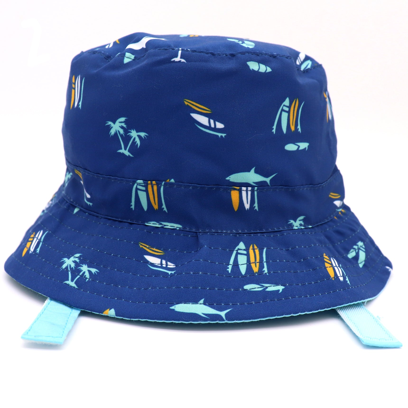 Kids bucket hat with built in UV protection, UPF 50+ for infants, toddler, and small children. Built in sun protection. Lightweight hat for sunny days, beach, pool, zoo, and playdates. Navy blue hat featuring palm trees, surfboards, and sharks in different solid colors, with baby blue Velcro straps. Reverses to solid baby blue hat.