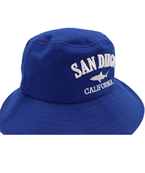 Front view of Royal Blue kids bucket hat featuring an embroidered design of a shark with verbiage San Diego above and California in white below it