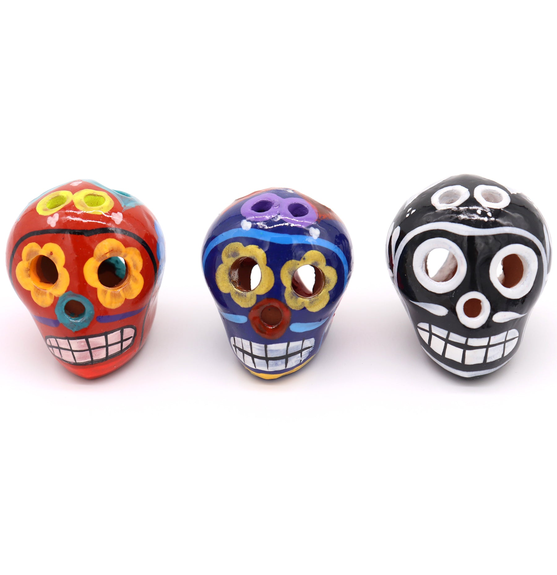 Sugar Skulls are handcrafted and hand painted with unique colorful features from Mexico. They come in sets of three, painted differently. First features an orange skull with flower eyes, teal flower on back and huge smile on front. Second with purple colors and flower. Third black and white.