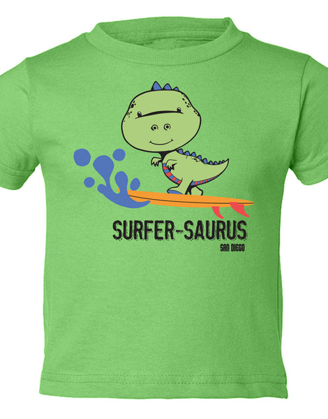 Boy Toddler surfing dinosaur t-rex apple color graphic t-shirt. Fun, Beautiful, Cool and Trendy design. Make an outfit for everyday wear, by local San Diego, California Artist. Design, Printed, and Sold by San Diego Trading Co.