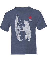Boys youth T-Shirt in Heather Denim Blue. Graphic Design by local San Diego, California Artist. Graphic tee features a rad cool tall bear holding a surf board inscribed with California and the letters S.D. on the left side with a red star on top. Simple and cool design for children. Sizes Small through X-large. Sold by San Diego Trading Co.