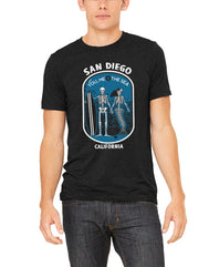 You me and the sea graphic tee with San Diego, California printed with white capital letters. Dog tag with blue background, man skeleton holding a surfboard and woman mermaid skeleton's hand. Top in capital white letters you, me and the sea. Graphic tee, design and printed by SDTrading Co.