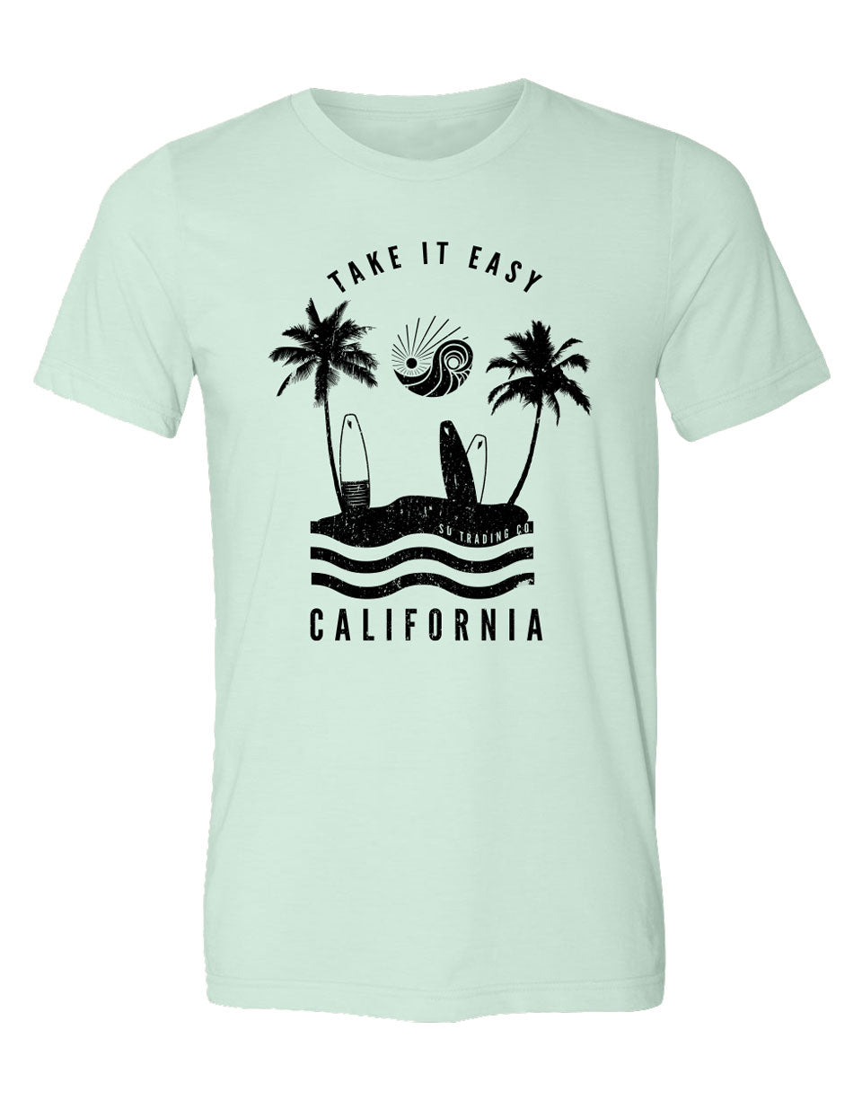 Take it easy California tee. Graphic shirt design by local artist in California, USA. Soft mint colored tee with black print. Two palm trees, surfboards, waves, and company logo above of sun and waves. Text at bottom California. Sold by local shop SDTrading Co.