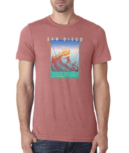 Adult mauve triblend short sleeve shirt with San Diego California in a square print of a surfer on a wave in a gradual orange to maroon print with blue white and aqua background
