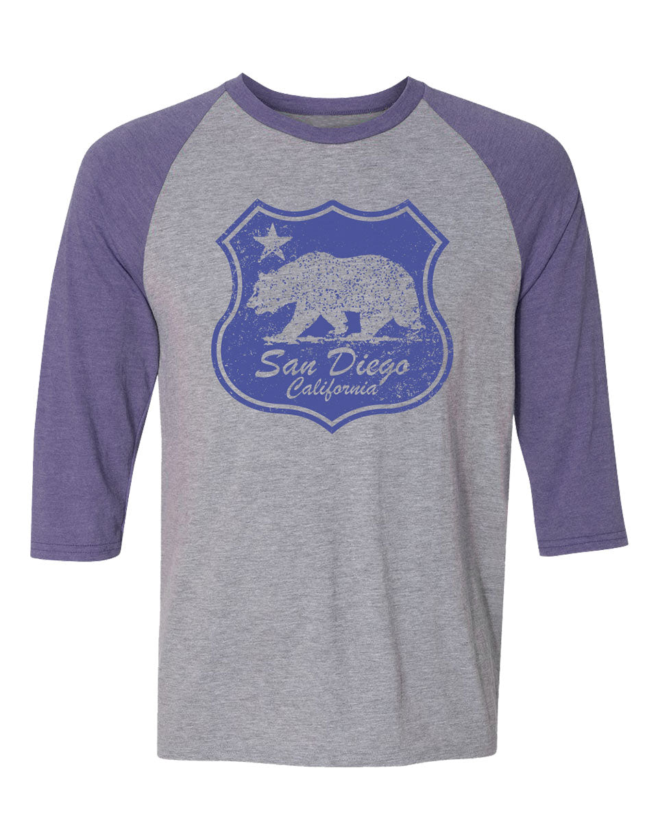 Adult heather grey raglan with royal blue sleeves featuring a blue shield design with the California bear and San Diego California Verbiage