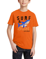 Boys youth crew neck T-Shirt  color orange. Graphic Design by local San Diego, California Artist. Graphic tee features a Blue smiling shark with text surf & sun makes it summer beach cool design for children. Sizes Small through X-large. Sold by San Diego Trading Co.
