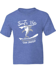 Boys graphic shark heather royal t-shirt. Graphic Design by local San Diego, California Artist. Graphic tee features a shark surfing on a board with text Surf Up San Diego. This comfy relax beach vibes shirt will make any little kid happy. Design, Printed, and Sold by San Diego Trading Co.