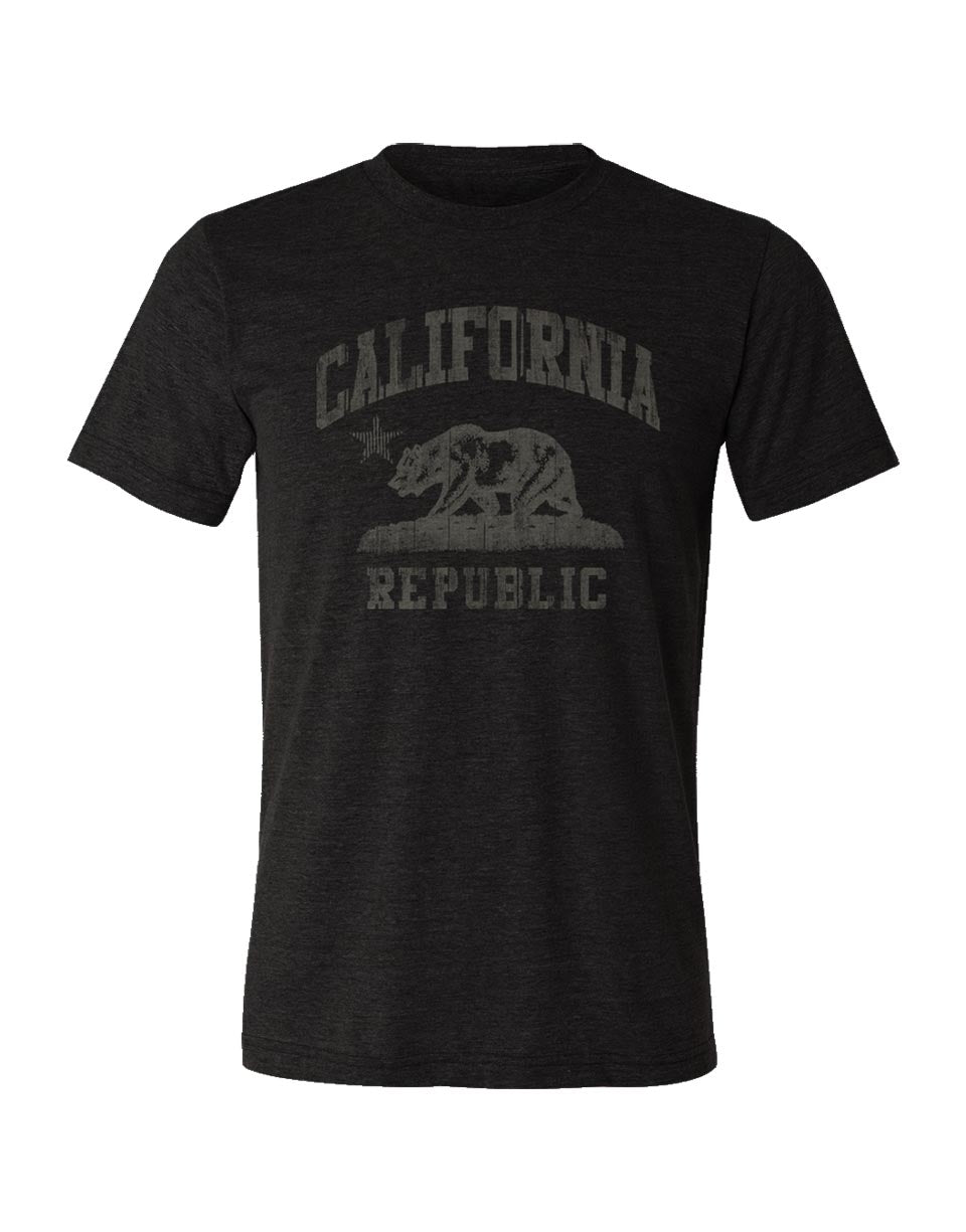 California Republic flag graphic tshirt for adult men or women. Printed on a premium vintage black soft triblend short sleeve tee, with distressed look. California bear standing over grass with California at top and Republic at bottom, all done with discharge to give it a faded look. Sold by local shop SDTrading Co.
