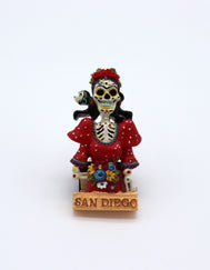 San DIego magnet featuring renewed Mexican artist Frida Kahlo sugar skull edition. Kahlo is seen with her red roses crown, skeleton head and rib cage, wearing a red dress with her pet on her shoulder. Bottom has San Diego painted. Sold by SDTrading Co.
