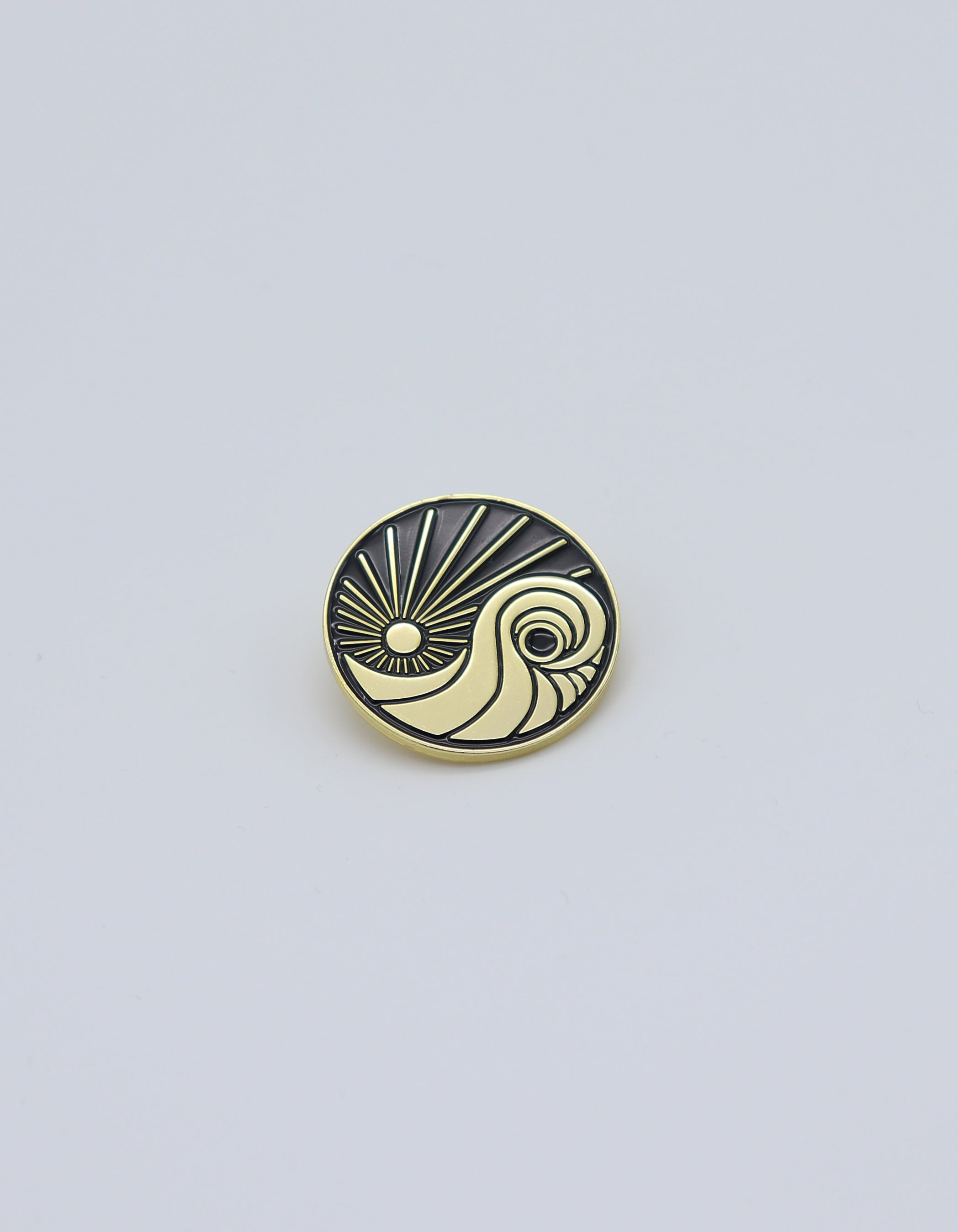 Gold colored circle pin featuring SD Trading Co's Logo against a black background. Sun and waves cool exclusive pin for your business blazer, t-shirt, backpack.