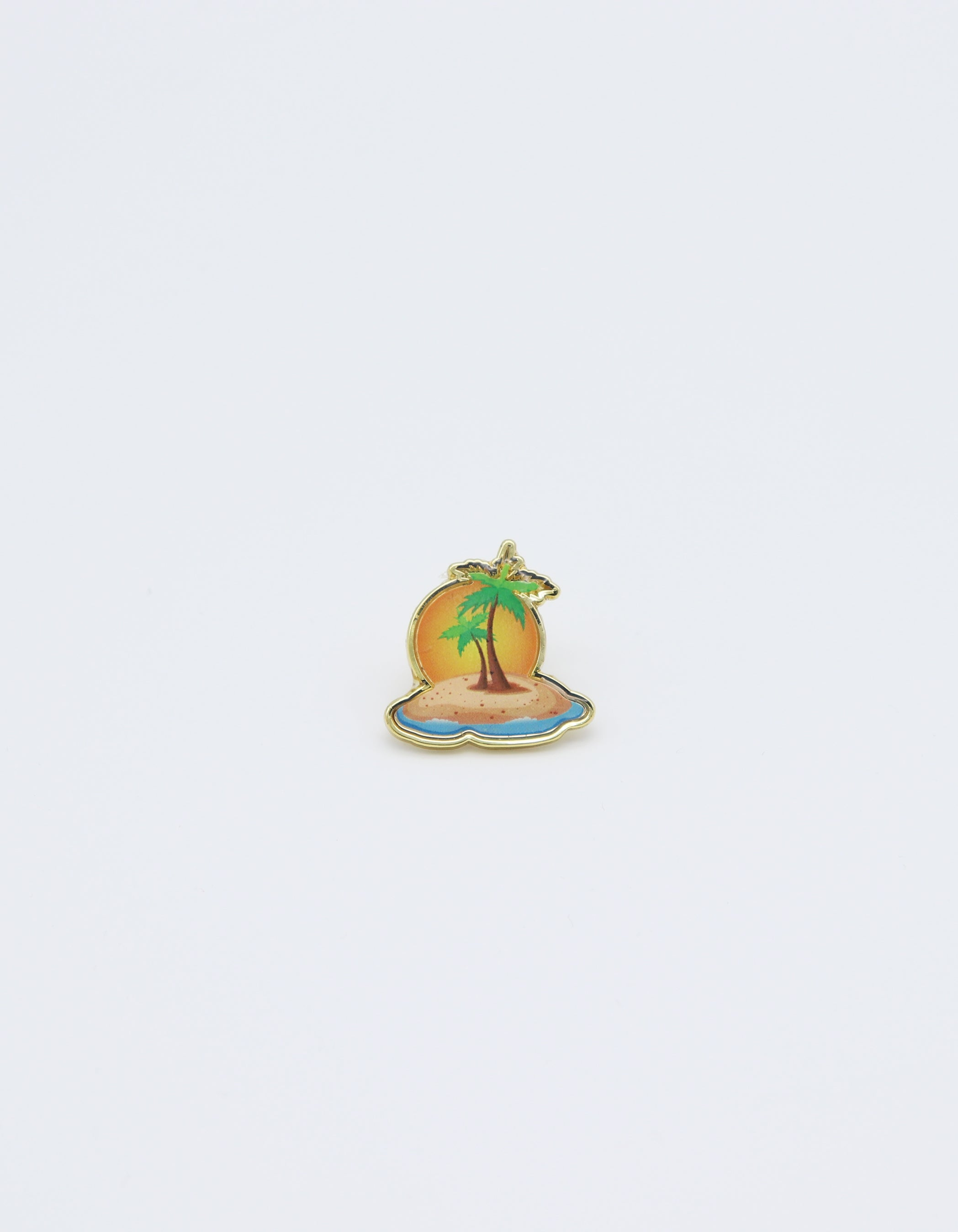 Tropical paradise Gold colored pin of island with palm tree surrounded by water in color gold sun, green palm trees, and sandy beach.