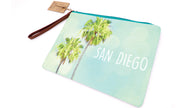 Women wallet clutch coins, keys, bills, passport or any traveling souvenirs your heart desires. Beautiful design palm trees and sea foam background and side white text San Diego. Zipper closure with brown pull handle.