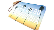 Women wallet clutch coins, keys, bills, passport or any traveling souvenirs your heart desires. Beautiful design palm trees blue sky top and yellow sunset color at bottom with white middle text San Diego, California. Zipper closure with brown pull handle.