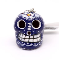 Clay sugar skull hand painted in blue, white white features and flower on top. Mexican art. Day of the dead celebration keychain for remembering loved one. Decorating altar. Sold by SDTrading Co.