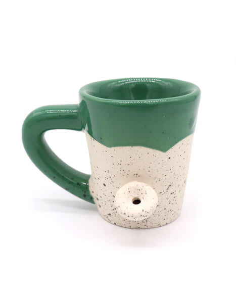 Bake and Wake Shot glass in a mini version of the mug but instead off coffee you can take a shot. Ceramic green top and handle, outer weed plant design, and print Potshots in cursive. Novelty gag gifts. Sold by SD Trading Co.