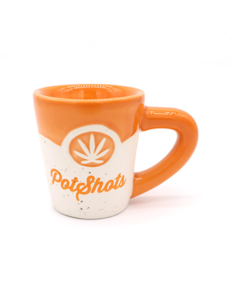 Bake and Wake Shot glass in a mini version of the mug but instead off coffee you can take a shot. Ceramic orange top and handle, outer weed plant design, and print Potshots in cursive. Novelty gag gifts. Sold by SD Trading Co.