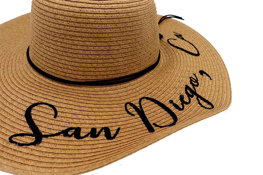 Women's beach hat, floppy hat with large rim that has great protection from sun. Great summer hat, vacation hat, or everyday hat. Beautiful straw sand color with decorative black strings all around and elastic band inside to keep hat on. San Diego, Ca. in large letters on top of hat.