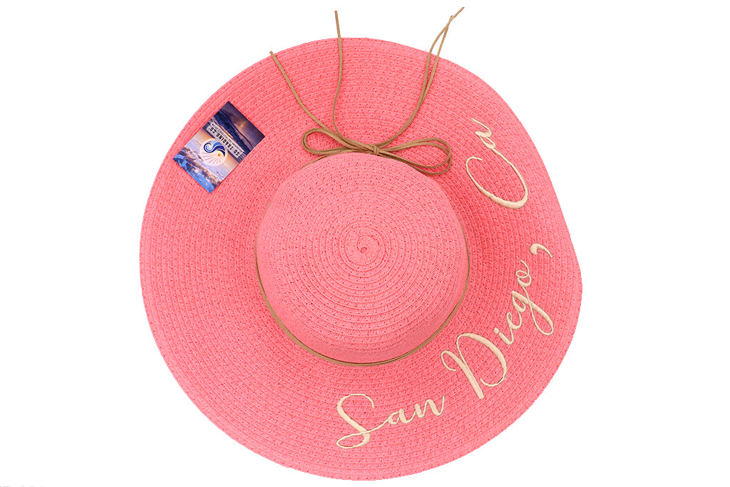 Top view of hat Women's beach hat, floppy hat with large rim that has great protection from sun. Great summer hat, vacation hat, or everyday hat. Beautiful pink color with decorative strings all around and elastic band inside to keep hat on. San Diego, Ca. in large gold letters on top of hat.