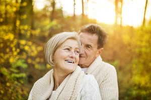 Older couple outside smiling in autumn