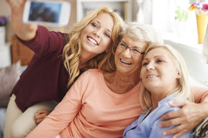 Mother, daughter, and grandmother taking selfie together in living room