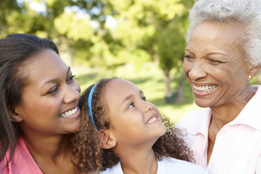 Mother, daughter and grandmother smiling together outside on a summer day