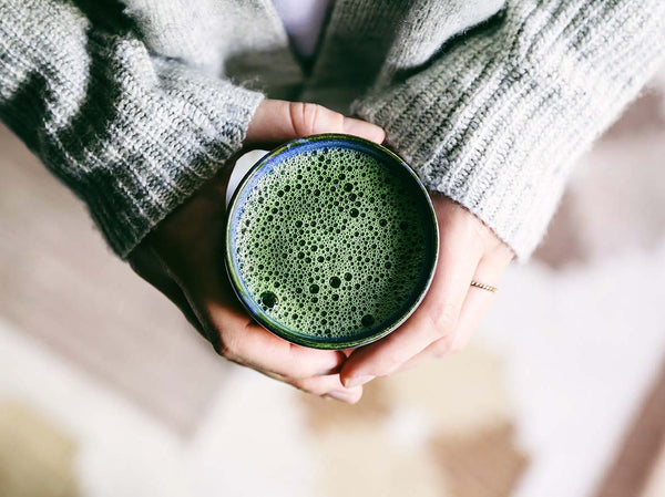 Holding a cup of organic matcha with bubbles