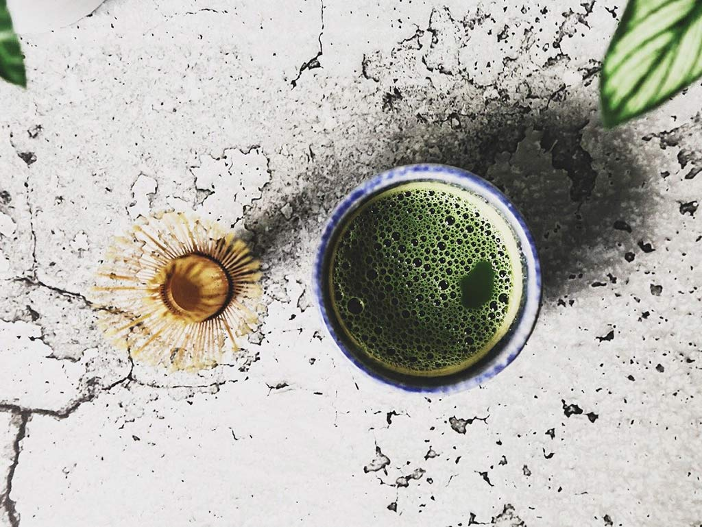Cup of organic matcha with whisk
