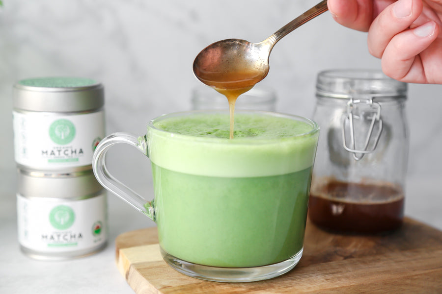 Honey being poured over a warm matcha latte