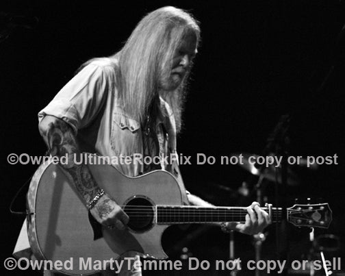 Photo of Gregg Allman of The Allman Brothers playing acoustic guitar in concert by Marty Temme