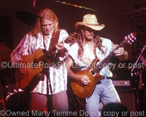 Photo of Gregg Allman and Dickey Betts playing guitar in concert in 1994 by Marty Temme