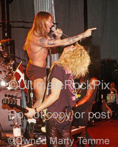 Photo of Axl Rose and Duff McKagan of Guns N' Roses in concert in 1990 by Marty Temme
