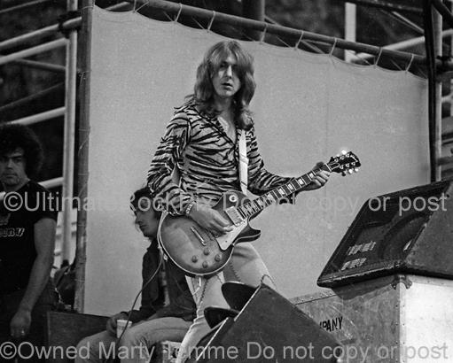 Black and white photo of Mick Ralphs of Bad Company playing a Gibson Les Paul onstage in 1974 by Marty Temme