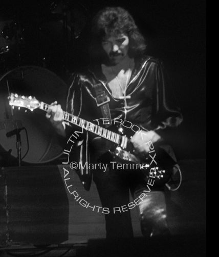 Photo of Tony Iommi of Black Sabbath in concert in 1976 by Marty Temme