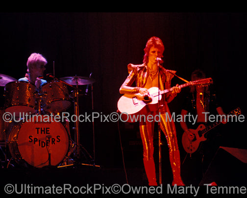Photo of David Bowie, Mick Ronson and Woody Woodmansey in concert in 1973 by Marty Temme