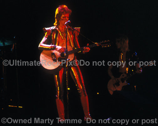 Photo of David Bowie playing acoustic guitar onstage in 1973 by Marty Temme