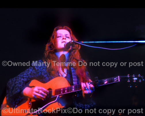 Photo of Bonnie Raitt playing a Gibson guitar in 1974 by Marty Temme
