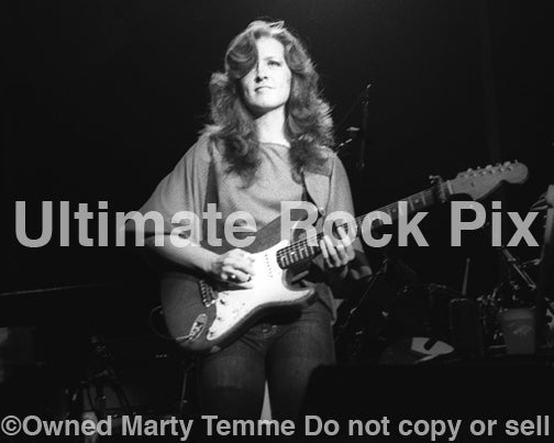 Black and white photo of guitarist Bonnie Raitt playing slide on a Fender Stratocaster in concert in 1980 by Marty Temme