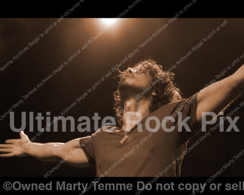 Photo of Chris Cornell with arms held out in concert in 2008 by Marty Temme
