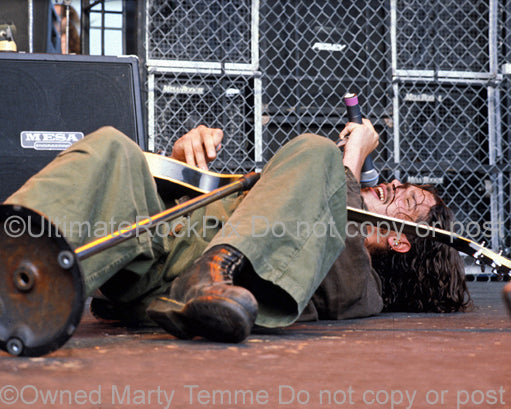 Photo of Chris Cornell of Soundgarden singing while lying down onstage in 1992 by Marty Temme