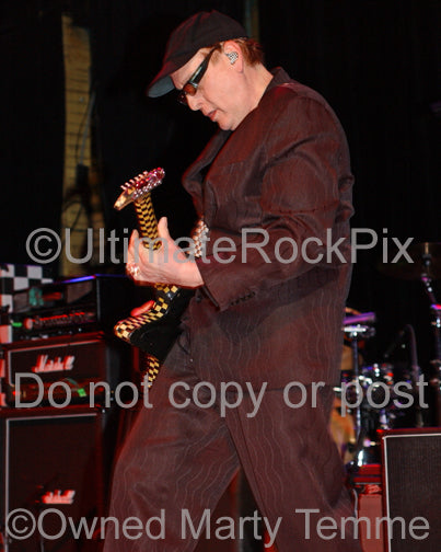 Photo of Rick Nielsen of Cheap Trick playing guitar in concert in 2006 by Marty Temme