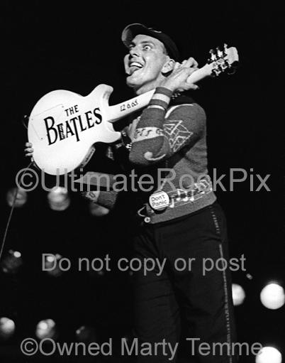 Photo of Rick Nielsen of Cheap Trick holding up his guitar with the words