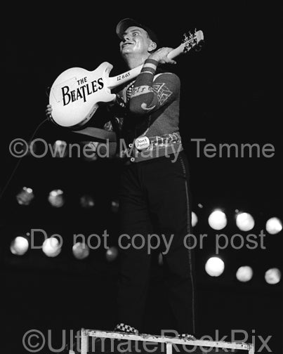 Photo of Rick Nielsen of Cheap Trick holding guitar with words