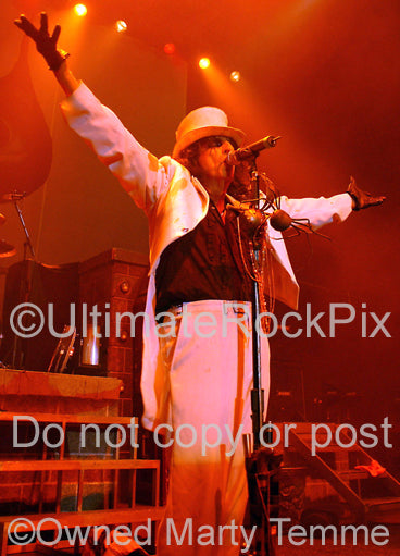 Photo of Alice Cooper in a white suit and top hat in concert in 2006 by Marty Temme