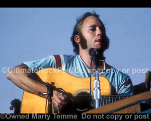 Photo of Stephen Stills of CSNY playing acoustic guitar in concert in 1974 by Marty Temme