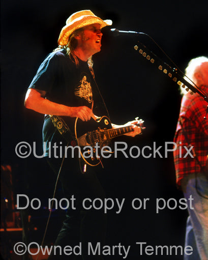 Photo of Neil Young playing his black Les Paul in concert by Marty Temme