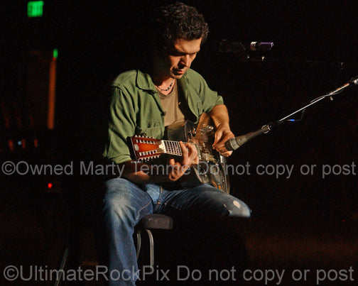 Photo of Doyle Bramhall II playing a 12 string resonator guitar in 2010 by Marty Temme