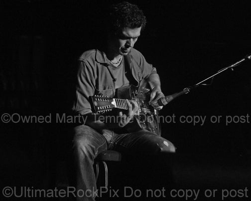 Black and white photo of Doyle Bramhall II playing a 12 string resonator guitar in 2010 by Marty Temme